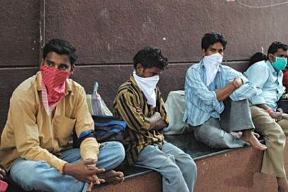 rail-passengers-cover-their-faces-outside-the-pune-railway-station