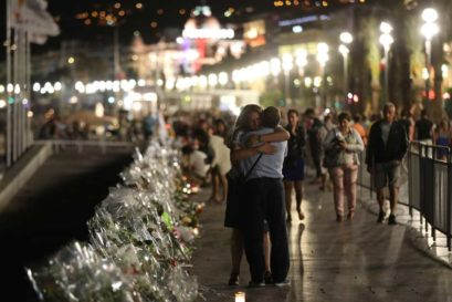 Two people hold each other by the new makeshift memorial on July 18, 2016 in Nice, in tribute to the victims of the deadly Bastille Day attack at the Promenade des Anglais