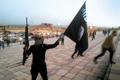 A fighter holds an Islamic State flag and a gun on a street in Mosul