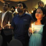 Alok Madasani (in dark blue), who was wounded in the shooting that left Srinivas Kuchibhotla dead, at a candlelight vigil in Olathe, Kansas