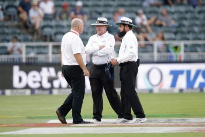 Umpires Ian Gould (C) Aleem Dar (R) and referee Andy Pycroft discuss ahead of suspending the match during the third day of the third test match