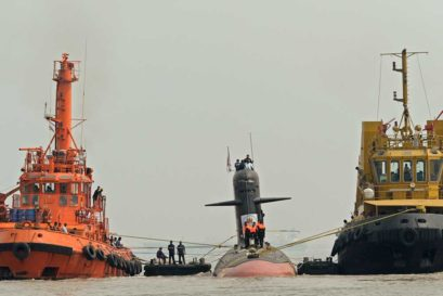 Tug boats escort the Scorpene submarine 'Kalvari' as it cruises into the Naval Dockyard in Mumbai on October 29, 2015