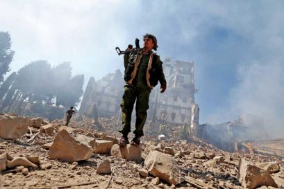 A Houthi fighter amidst the rubble of an air strike in Sana'a, Yemen