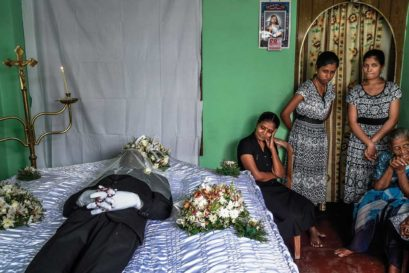 Delcia Fernando mourns with her daughters in front of the body of her husband at her house near St Anthony's Church in Colombo